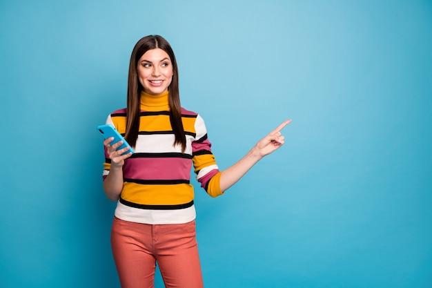 ポジティブガールポイント人差し指使用スマートフォンの肖像画は、割引直接広告ソーシャルネットワークプロモーションを着用する青い色の壁に分離された赤いスタイリッシュな流行の服を着用することをお勧めします