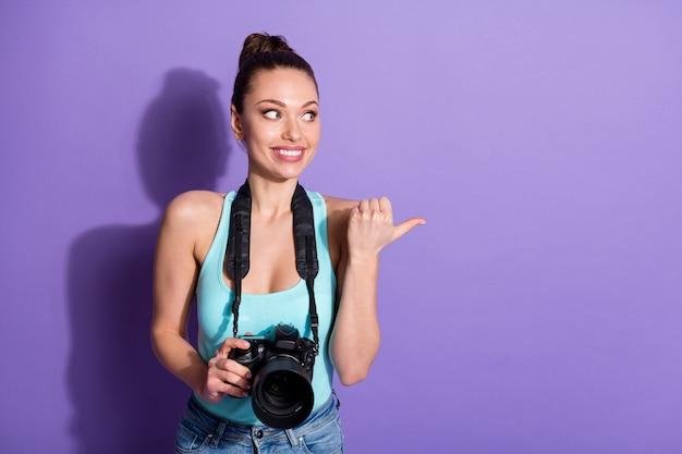 긍정적인 여자 여행자의 초상화는 디지털 카메라 포인트 엄지 손가락 copyspace를 잡고