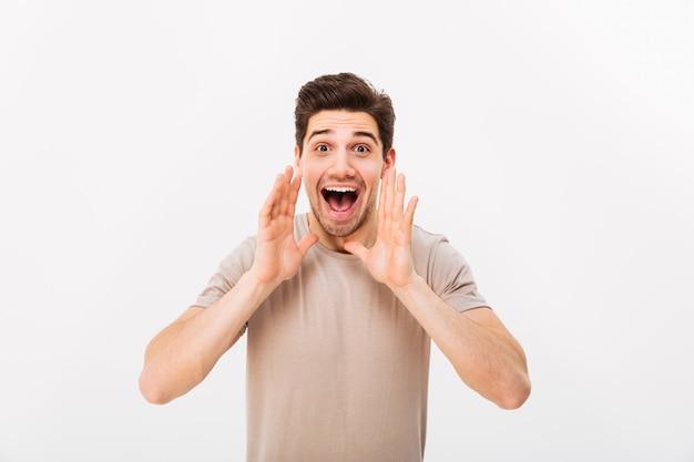 剛毛と茶色の髪の叫びまたは白い壁に分離された口に手で呼び出すと肯定的な男の肖像