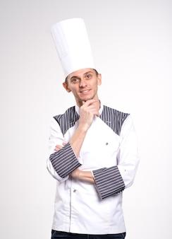 Портрет положительного красивого кашевара шеф-повара в берете и белом обмундировании изолированном на белой предпосылке.