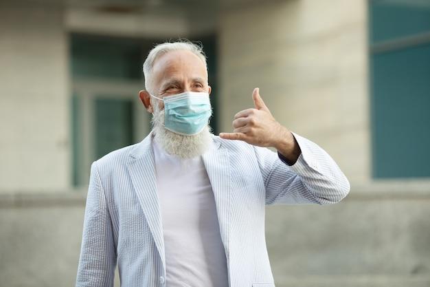 フレンドリーな笑顔と手を振って医療マスクを持つポジティブなハンサムなシニアビジネスマンの肖像画