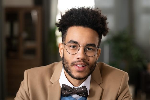 점선 나비 넥타이와 홈 오피스에 앉아 둥근 모양의 안경을 쓰고 아프리카 헤어스타일을 가진 긍정적인 잘 생긴 젊은 흑인 남자의 초상화