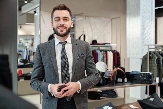 Портрет позитивного красивого молодого бизнесмена с бородой, держащего смартфон в магазине одежды