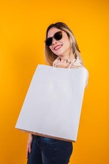 Портрет позитивной счастливой белокурой девушки, весело проводящей время за покупками на желтом фоне.