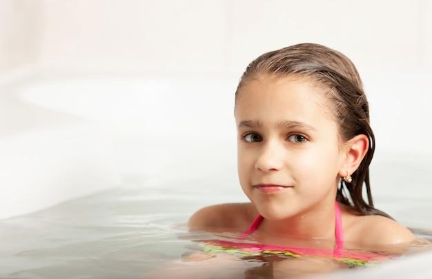 Портрет позитивной маленькой улыбающейся кавказской девушки в купальнике