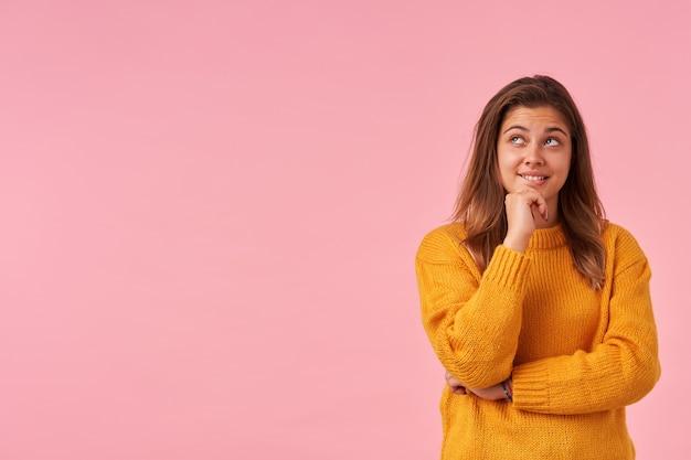 ピンクのマスタードニットセーターを着て、彼女のあごを保持し、夢のように上向きに見えるナチュラルメイクのポジティブな素敵な若い茶色の髪の女性の肖像画