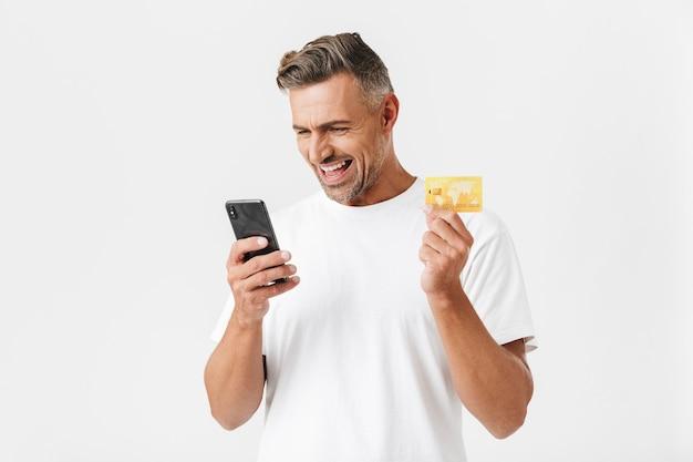 Портрет позитивного мужчины 30-х годов в повседневной футболке со смартфоном и пластиковой кредитной картой, изолированной на белом