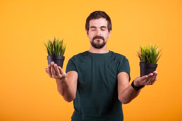평온한 마음의 긍정적인 남자의 초상화는 노란색 배경에 푸른 잔디가 있는 두 개의 냄비를 들고 있습니다. 자연 컨셉 사진과의 연결. 그의 눈은 감겨있다