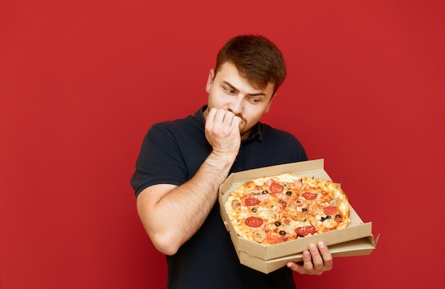 긍정적 인 남자의 초상화는 서서 맛있는 신선한 피자 상자를 엽니 다