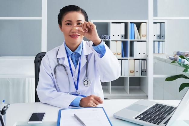 Портрет положительного зрелого врача показывает таблетку омеги или рыбьего жира, которую она рекомендует принимать ежедневно