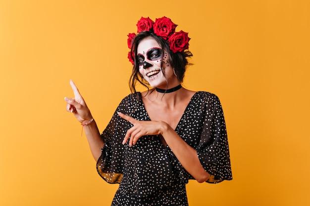 텍스트에 대 한 공간을 가진 주황색 배경에 긍정적 인 멕시코 여자의 초상화. 두개골 마스크를 가진 여자가 귀엽게 미소 짓고 손가락을 가리 킵니다.