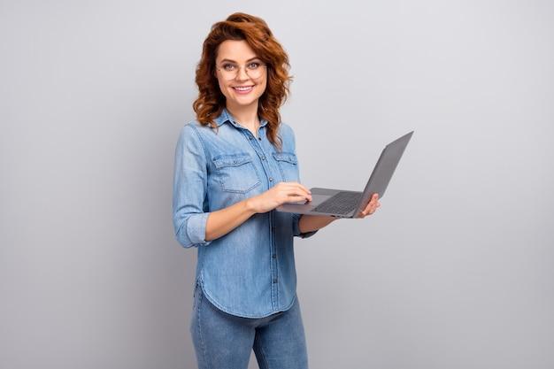 Портрет позитивной современной женщины-менеджера, использующей ноутбук, готовый общаться с онлайн-клиентами, партнеры носят красивую одежду, изолированную на стене серого цвета