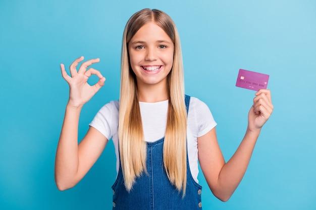 Портрет позитивной девушки со светлыми волосами, держащей банковскую карту, показывает знак `` ок '' купить на продажу, изолированные на пастельно-синем цветном фоне