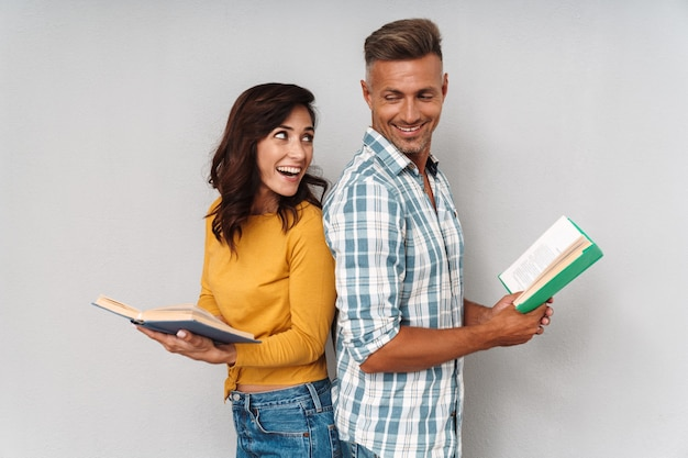 Портрет позитивной оптимистической счастливой улыбающейся взрослой любящей пары, изолированной над серой стеной, читающей книгу.