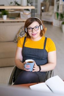 Портрет позитивной красивой девушки в беспроводных наушниках, сидящей в инвалидной коляске