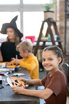 Портрет позитивной красивой девушки, сидящей за столом против учителя и одноклассника и создающей поделку из тыквы на хэллоуин в художественном классе