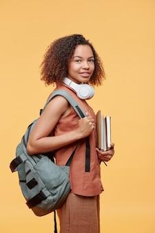 黄色の背景にワークブックのスタックを保持している背中にランドセルを身に着けている巻き毛のポジティブなかわいい学生の女の子の肖像画