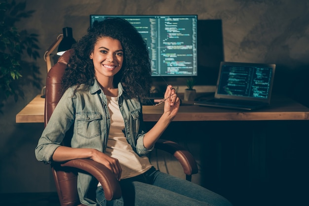 Портрет позитивной опытной девушки сидит в кресле, позирует в офисе