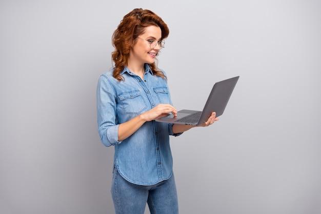 Портрет позитивной, умной профессиональной женщины-менеджера, использующей компьютерный поиск в социальных сетях, общение в чате, одетая в красивую одежду, изолированную на стене серого цвета