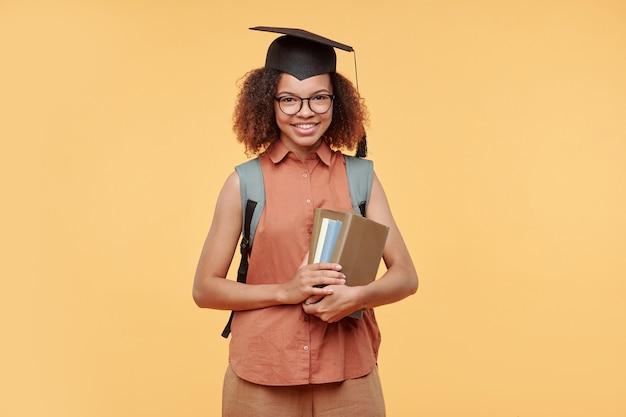 黄色の背景に本のスタックを保持しているキャップで肯定的な成功した黒人大学院生の肖像画