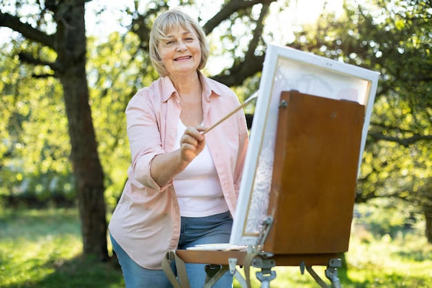 緑豊かな公園の屋外でイーゼルの前に立ち、筆を持ち、絵を描いているポジティブな才能のある中年女性アーティストのポートレート。創造性、インスピレーション、アート、絵画のコンセプト。