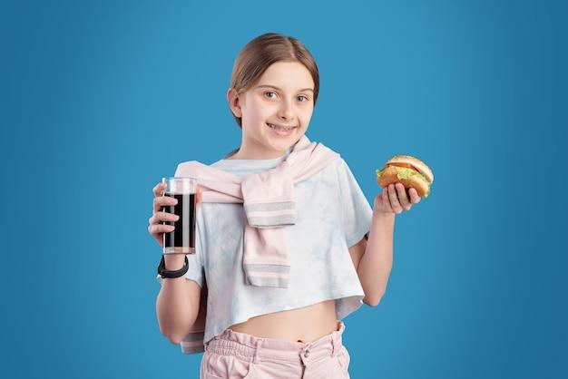 不健康なハンバーガーを食べてコーラを飲むポジティブな10代の少女の肖像画