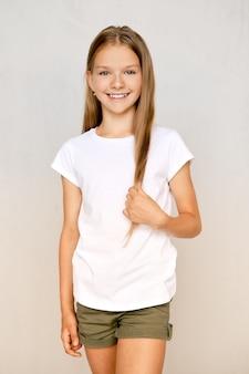 Портрет позитивной девочки-подростка, стоящей со скрещенными ногами и трогательными волосами
