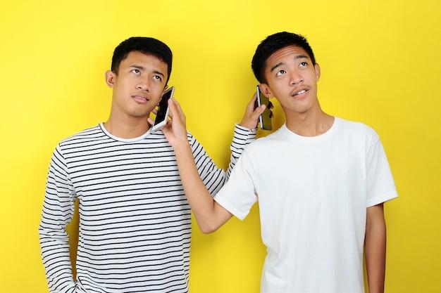 긍정적인 두 아시아 남성의 초상화는 서로의 휴대폰을 들으며 복사 공간이 격리된 노란색 배경을 봅니다.