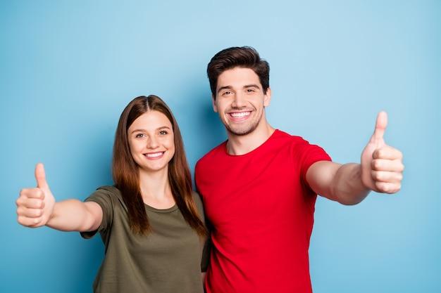 Портрет позитивных двух супругов, промоутер показывает большой палец вверх рекомендую рекламу давать советы по выбору носить повседневную одежду, изолированную на синем цветном фоне Premium Фотографии