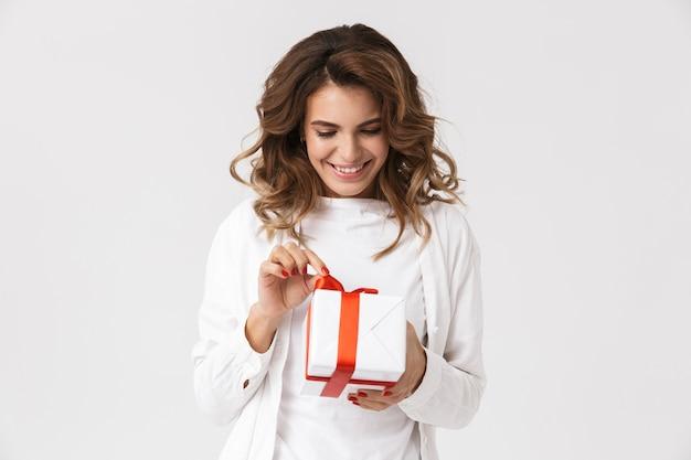 Портрет позитивной женщины в повседневной одежде, держащей подарочную коробку, изолированную