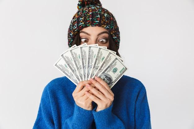 Портрет позитивной женщины в зимней шапке, держащей веер долларовых денег стоя, изолированной на белом
