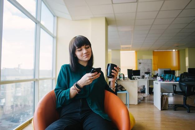 笑顔で電話を見て近代的なオフィスに座っている肯定的な若いビジネス女性の肖像画。