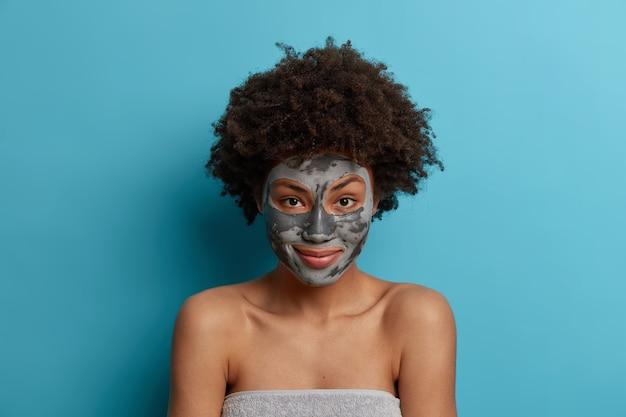 얼굴 점토 마스크가있는 긍정적 인 젊은 여성 모델의 초상화는 미용 제품을 사용하고 직접 보이며 목욕 타월에 싸여 피부와 안색을 걱정하며 상쾌한 표정을 가지고 있습니다.