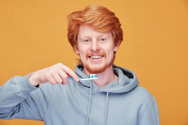 オレンジ色の歯ブラシで歯を掃除するパーカーのポジティブな若い赤毛の男の肖像画
