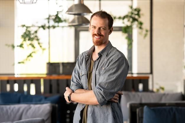 Портрет позитивного молодого владельца малого бизнеса с бородой, стоящего со скрещенными руками в собственном кафе