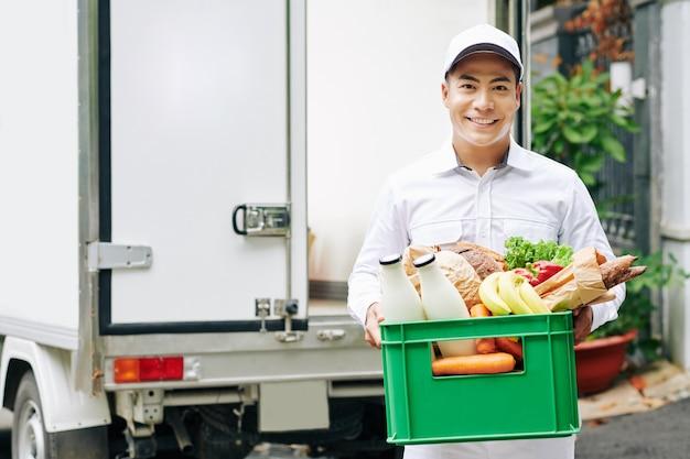 신선한 과일, 빵, 병에 든 우유와 함께 플라스틱 상자를 들고 긍정적 인 젊은 베트남 택배의 초상화