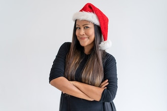Portrait of positive young woman in Christmas hat