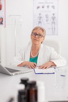 病気の丸薬治療で働いている会議会議室の机に座ってカメラを見ている開業医の年配の女性医師の肖像画。医療の専門知識を提示する自信のある医師