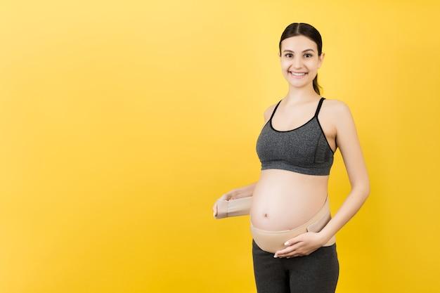 복사 공간 노란색 표면에 탄성 출산 밴드를 드레싱 임신 한 여자의 초상화