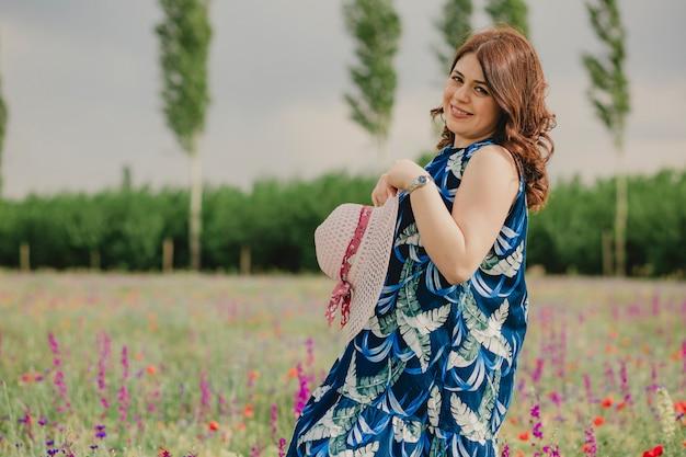 夏の花がいっぱいの野原で帽子をかぶり、暖かい気候を楽しむ妊婦のポートレート