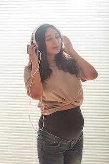 집에서 창문 근처에 있고 헤드폰으로 음악을 듣는 임산부의 초상화. 임신과 여가 개념.