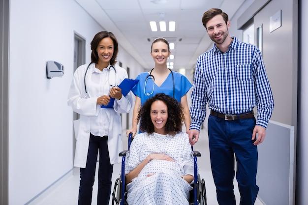 Портрет беременной женщины, сидя на инвалидной коляске в коридоре