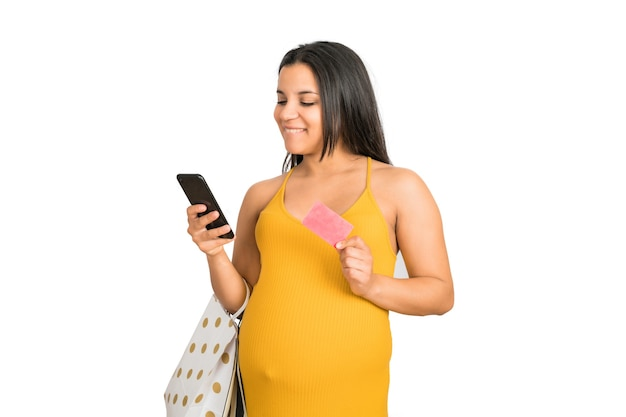 白い背景の上のオンラインショッピングにクレジットカードと携帯電話を使用して妊娠中の女性の肖像画。オンラインコンセプトを購入します。