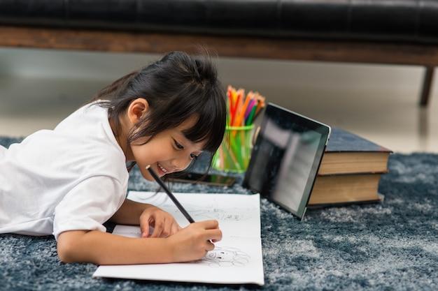 宿題にタブレットを使用している就学前の子供の肖像画、インターネット上のデジタルタブレット検索情報を使用して宿題をしている子供のソフトフォーカス、eラーニングまたはホームスクーリング教育の概念