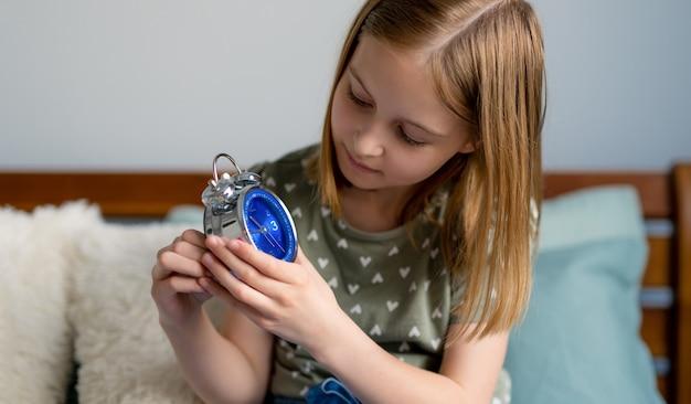寝室の女性の子供の女子高生シッティの青い時計とプレティーンの美しいブロンドの髪の少女の肖像...