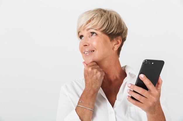 コピースペースで微笑んで、スタジオで白い壁に隔離された携帯電話を保持している短いブロンドの髪を持つかなり大人の女性の肖像画