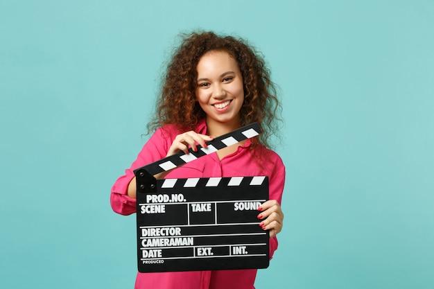 파란색 청록색 배경에 격리된 클래식 블랙 필름 제작 클래퍼보드를 들고 평상복을 입은 예쁜 아프리카 소녀의 초상화. 사람들은 진심 어린 감정, 라이프 스타일 개념입니다. 복사 공간을 비웃습니다.