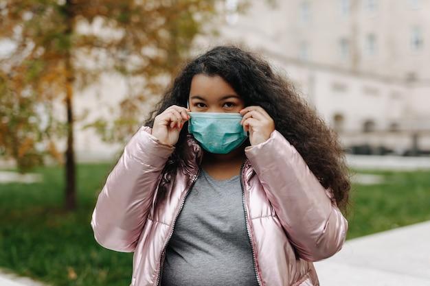 医療用フェイスマスクで路上でポーズをとってかわいいアフリカの女性の肖像画。感染症から身を守る黒髪の若い女性。