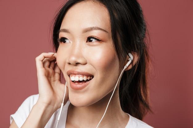 기본적인 옷을 입은 예쁜 아시아 여성의 초상화는 웃고 있고 빨간 벽에 격리된 이어폰으로 음악을 들으며