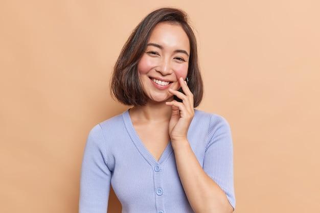 優しい笑顔の可愛いアジア人女性のポートレートは、カジュアルな青いジャンパーに身を包んだ表情を満足させています。
